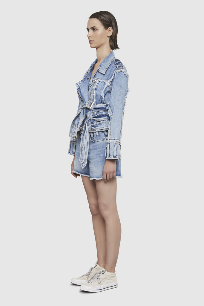 A woman is wearing a NTMB denim frayed jacket by Faith Connexion, a brand of luxury clothes