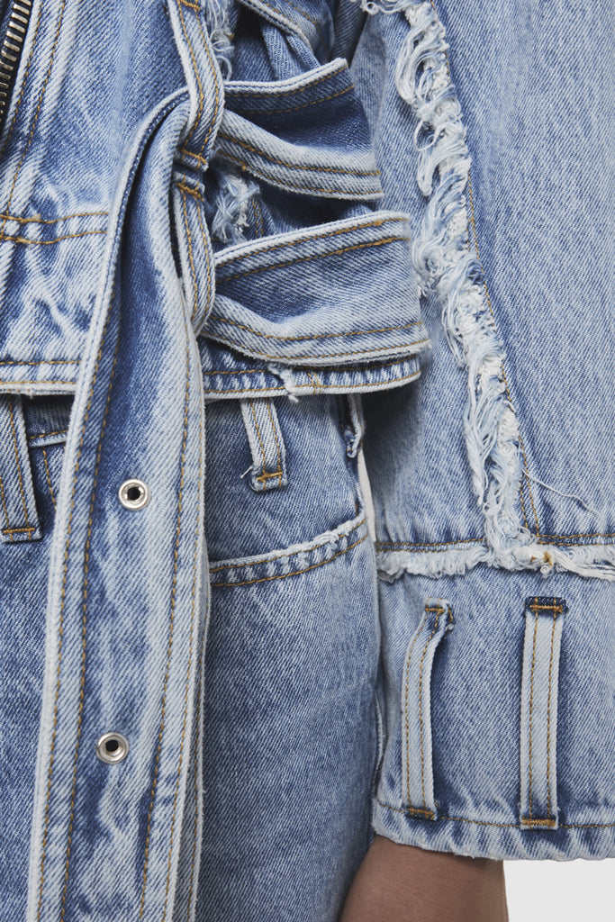 A close-up of a NTMB denim frayed jacket by Faith Connexion, a brand of luxury clothes