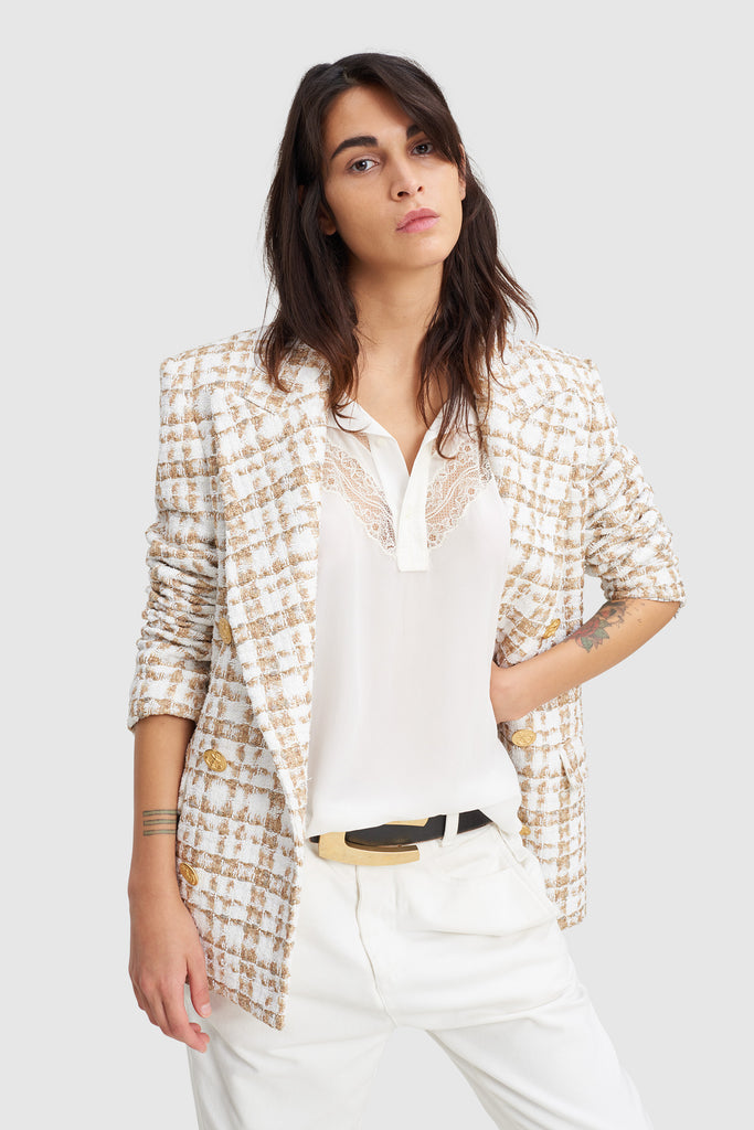 A woman is wearing a 90's tweed jacket by Faith Connexion, a brand of luxury clothes