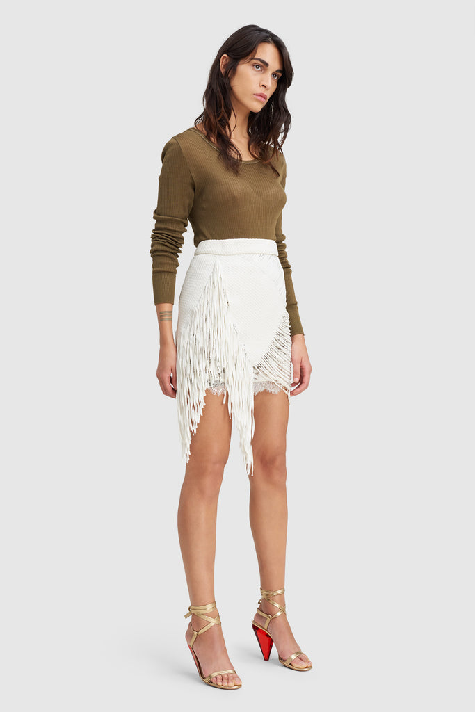 A woman is wearing a white fringe braid skirt by Faith Connexion, a brand of luxury clothes