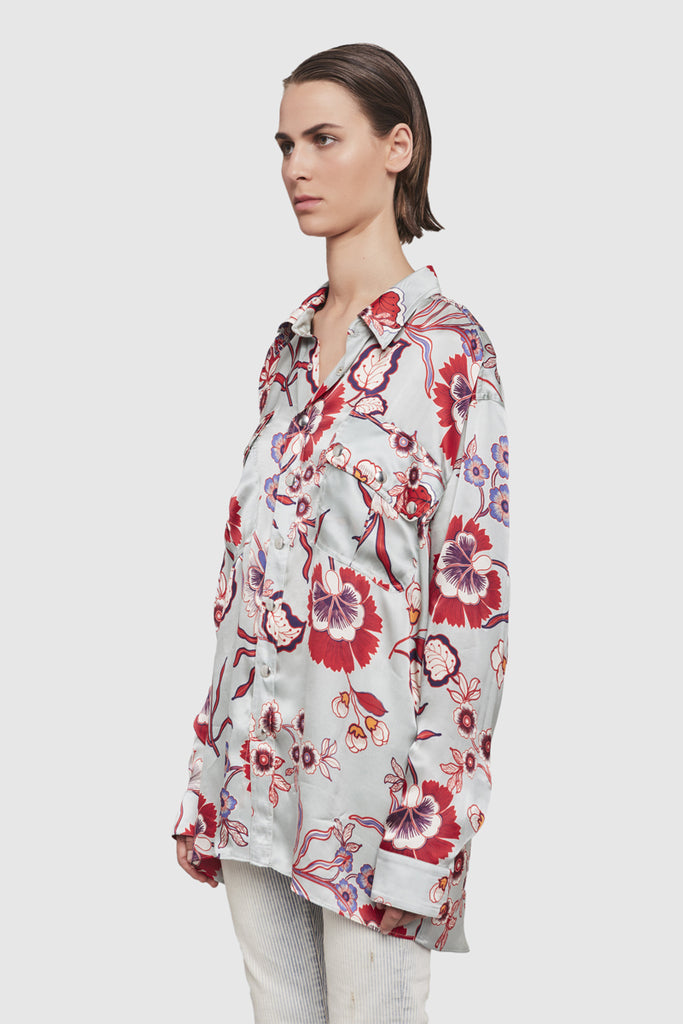 A woman is wearing a pyjama-style collar shirt embellished by indian floral print by Faith Connexion, a brand of luxury clothes