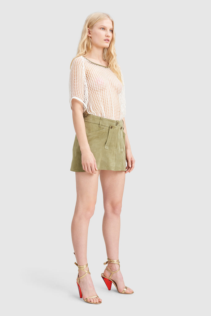 A woman is wearing a green khaki peach skin mini skirt by Faith Connexion, a brand of luxury clothes