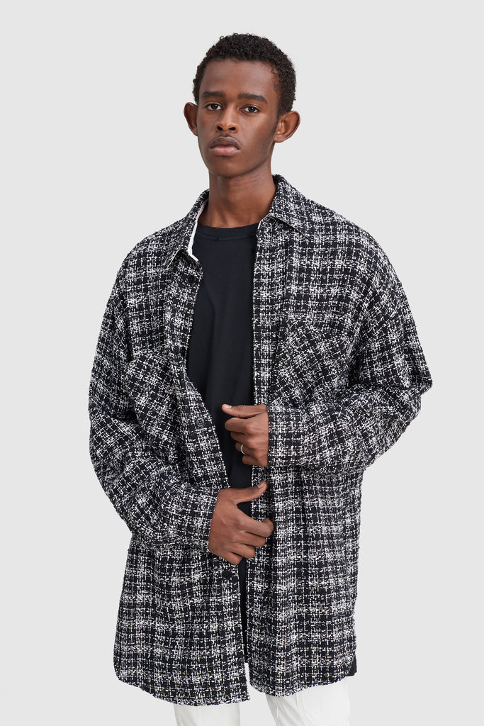 A man is wearing a black tweed oversize shirt by Faith Connexion, a brand of luxury clothes