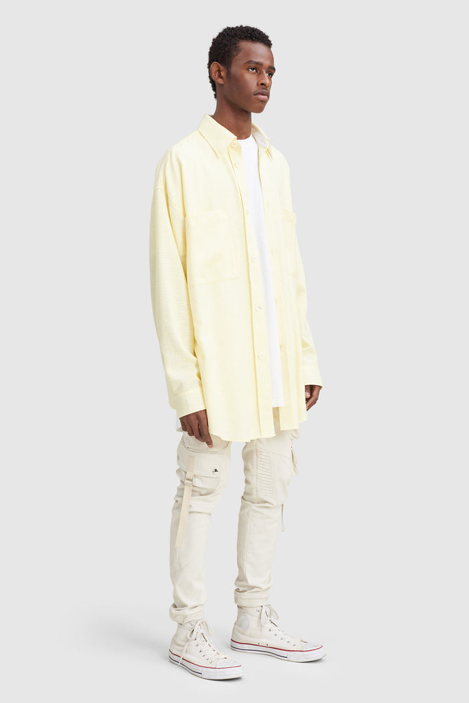 A man is wearing a yellow tweed oversize shirt by Faith Connexion, a brand of luxury clothes