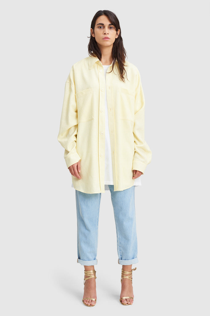 A woman is wearing a yellow tweed oversize shirt by Faith Connexion, a brand of luxury clothes