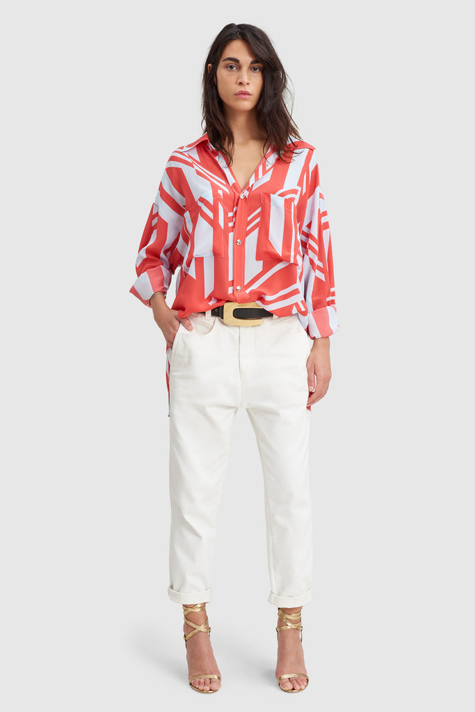 A woman is wearing a geometric print silk overshirt by Faith Connexion, a brand of luxury clothes