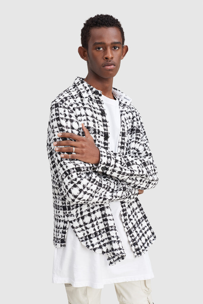 A man is wearing a black and white checked tweed overshirt by Faith Connexion, a brand of luxury clothes