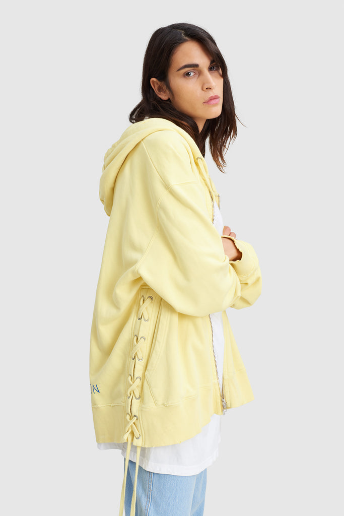 A woman is wearing a yellow laced oversize hoodie sweat by Faith Connexion, a brand of luxury clothes