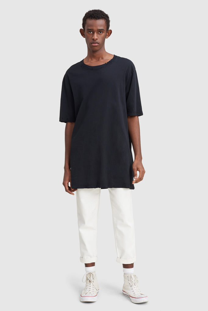 A man is wearing a black oversize t-shirt by Faith Connexion, a brand of luxury clothes