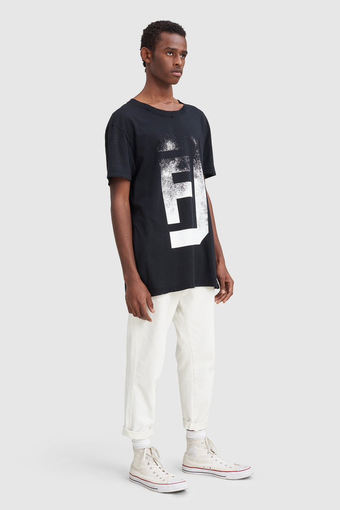 A man is wearing an oversize t-shirt by Faith Connexion, a brand of luxury clothes