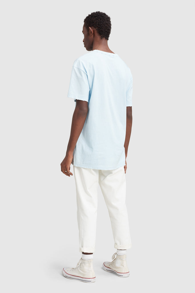 A man is wearing a light blue t-shirt by Faith Connexion, a brand of luxury clothes