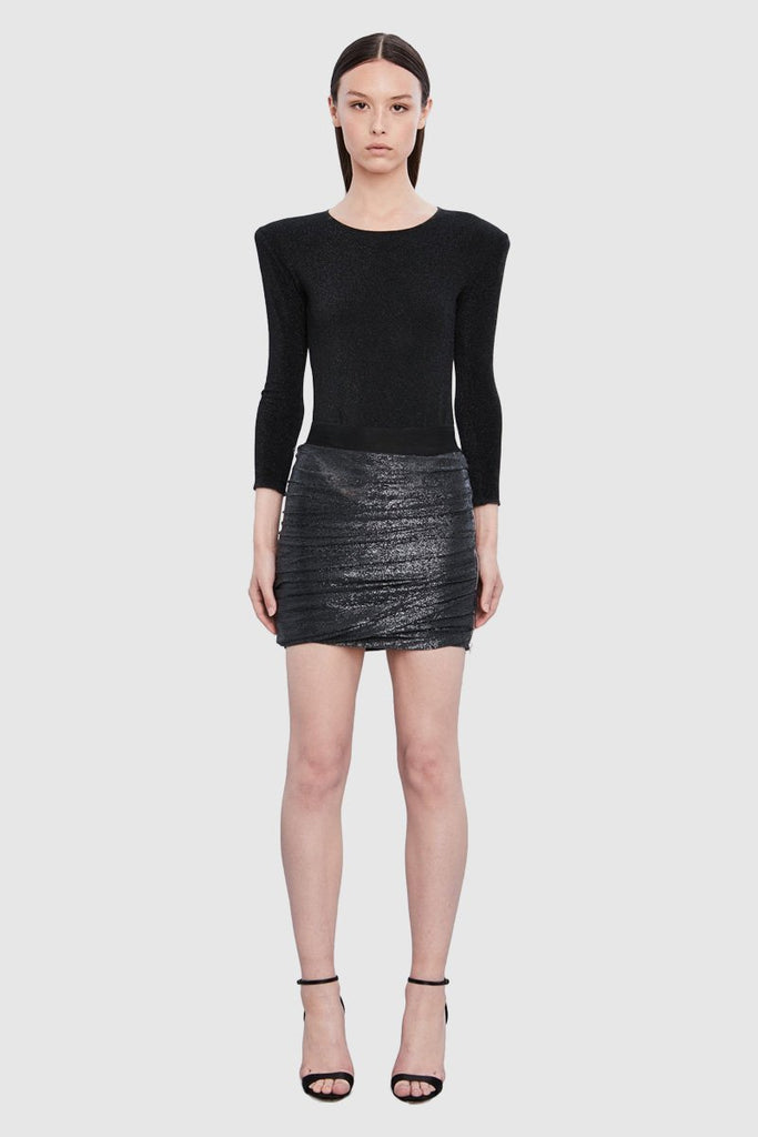 A woman is wearing a black drape tube mini skirt by Faith Connexion, a brand of luxury clothes