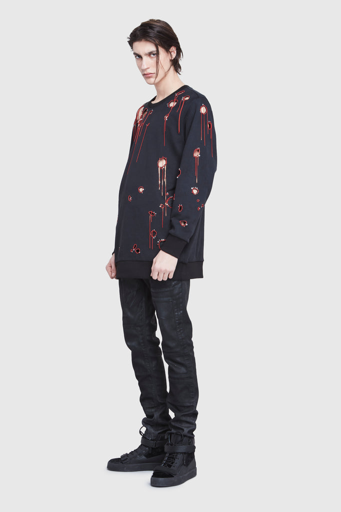 Three quarter. A man is wearing a black cotton oversized sweater with holes and embroidery by Faith Connexion, a brand of luxury clothes