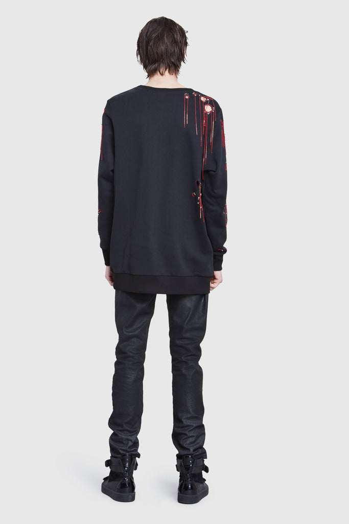 A man is wearing a black cotton oversized sweater with holes and embroidery by Faith Connexion, a brand of luxury clothes