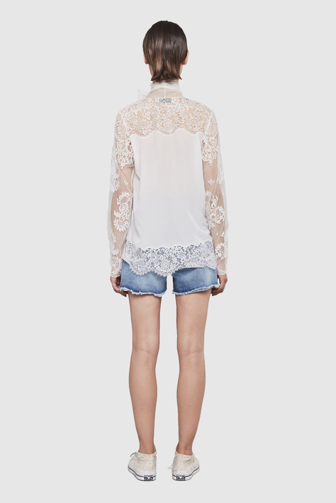 A woman is wearing a white lace laval top by Faith Connexion, a brand of luxury clothes