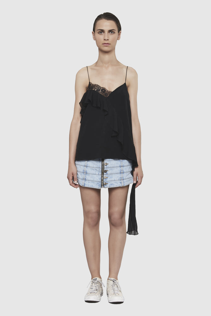 Full length picture. A woman is wearing a black lingerie top by Faith Connexion, a brand of luxury clothes