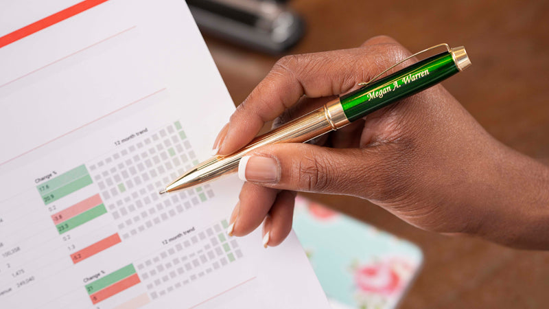 Personalized Braxton ballpoint in green over budget and earnings charts. Braxtons make tone of the best options for promotional pens and impressing corporate clients.