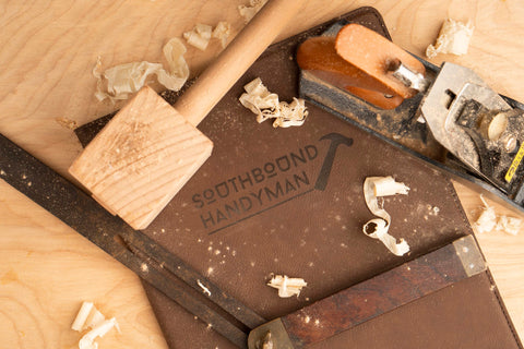A brown engraved gifts padfolio with logo engraving covered in woodcarving tools and wood shavings