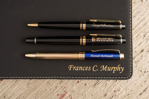 A Waterman Expert ballpoint pen with signature engraving, a Waterman Expert Fountain Pen with logo engraving, and a Dayspring Pens green Braxton ballpoint pen with personalized engraving rest on a black engraved gifts padfolio
