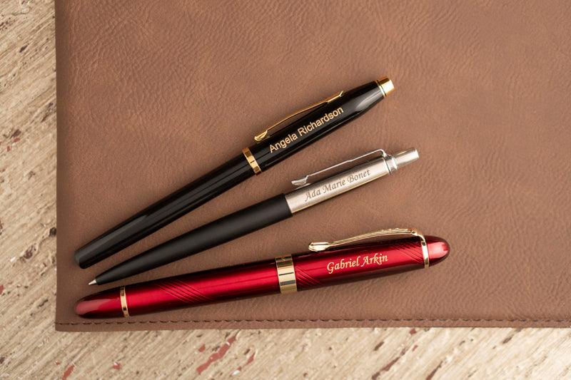 Cross century II black gold capped pen, Parker Jotter black gel pen, Dayspring Pens Arizona red capped pen with personalization arrayed on brown note pad. A selection of perfect pens for friends, promotional purposes, client relations, or corporate gifts.