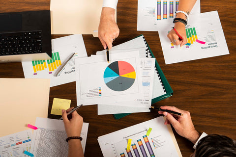 Professional People holding Personalized Pen gifts over budget charts
