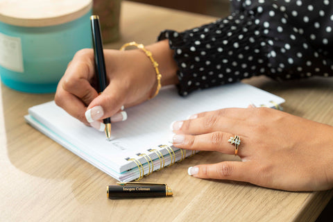 A woman writes with a Waterman Hemisphere rollerball pen