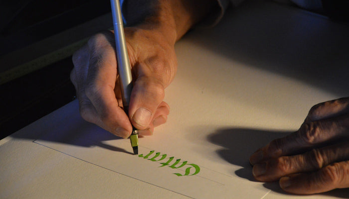 person writing using calligraphy-pen