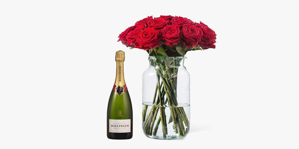 Bottle of champagne next to jar of long-stemmed red roses