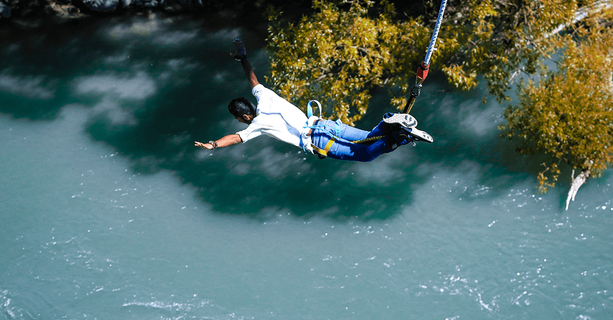 A man bungee jumping over a light blue river