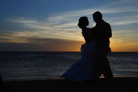 silhouette of man and woman on the beach during sunset