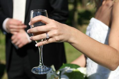 lady holding champagne glass with engagement ring