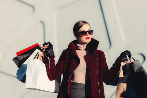 lady wearing sunglasses with shopping bags in both hands