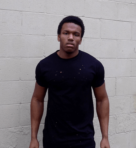dark skinned male standing in black tshirt
