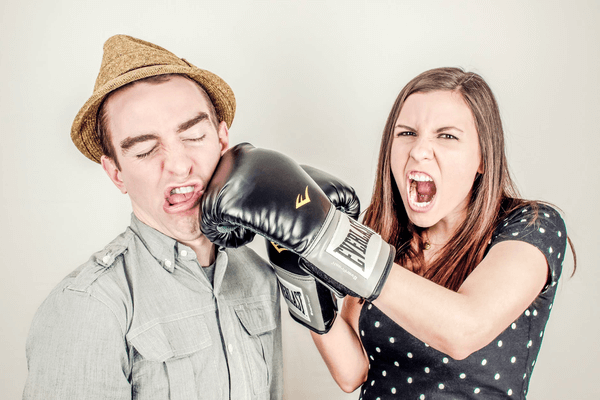 girl punching guy on the face with boxing glove