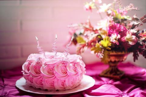 yummy looking cake with pink icing and pink candles with wild native flowers in a vase in the background