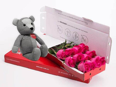 cute grey teddy bear sitting next to a box of medium stemmed bright pink roses from mr roses
