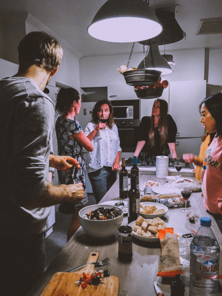 group of friends standing around the dinner table with food and drinks in hand