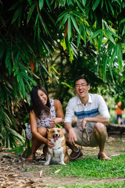 couple and their dog laughing and posing for a picture under a tree with vibrant green leaves