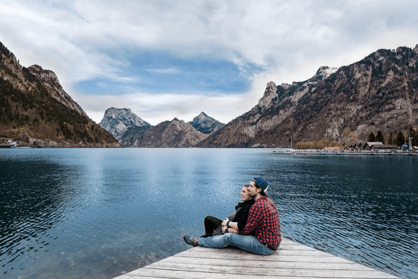 couple sitting on the edge of walk way with legs in water staring at the mountains