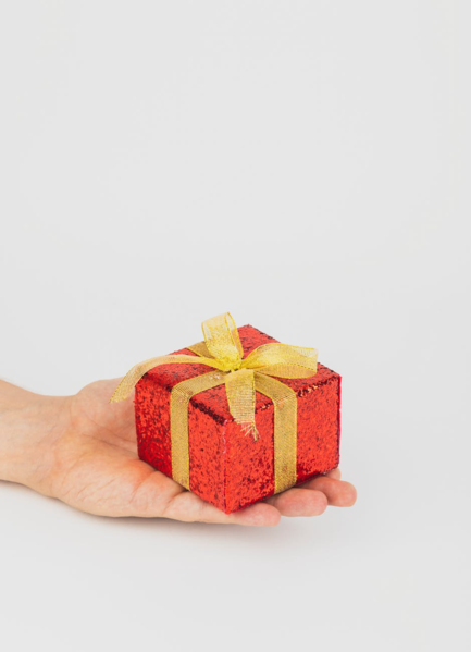 tiny red gift box with yellow ribbon bow
