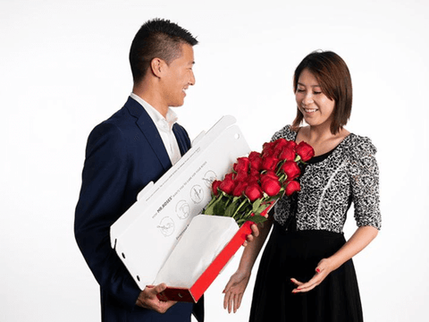 man giving his lady love a box of long stem beautiful bright red roses from mr roses
