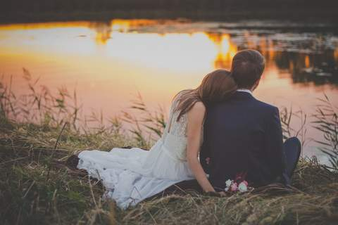 couple sitting at the edge of a pond staring into sunset