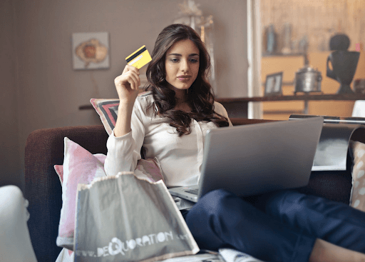 lady is holding a credit card to online shop