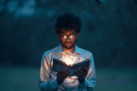 guy reading a book in the dark with fairy lights
