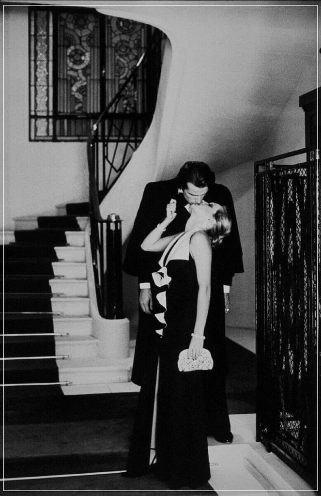 """Man Leaning to Kiss Woman at Base of Staircase"" by Helmut Newton Photography-Artography Limited"