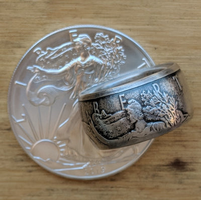 Fat Tire shaped Silver Eagle Coin Ring with patina resting on a Silver Eagle coin.