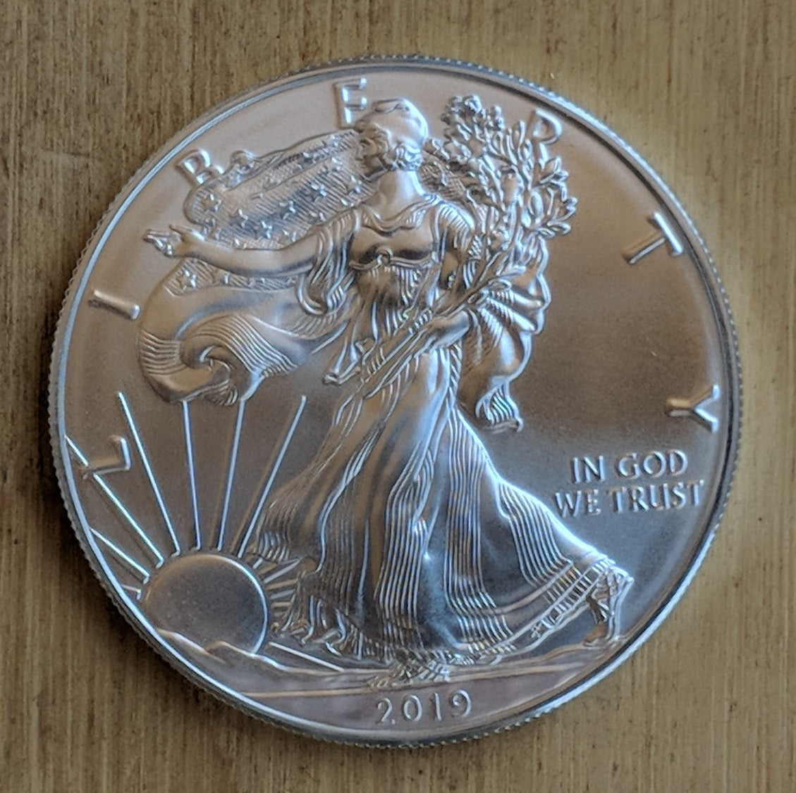 Silver Eagle bullion coin with Lady Liberty striding toward the rising sun.