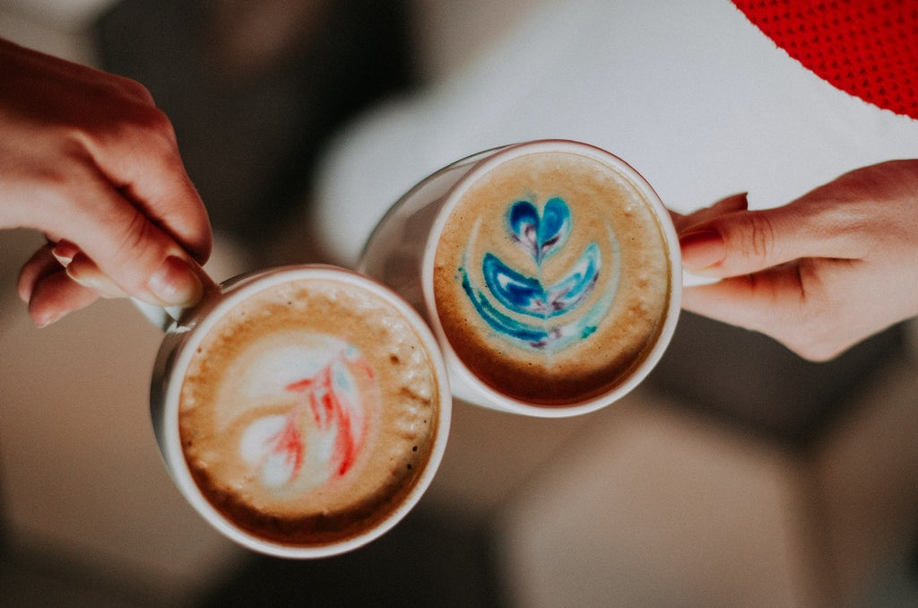 Two cups of colorful fresh cappuccino brews with pink and blue hues