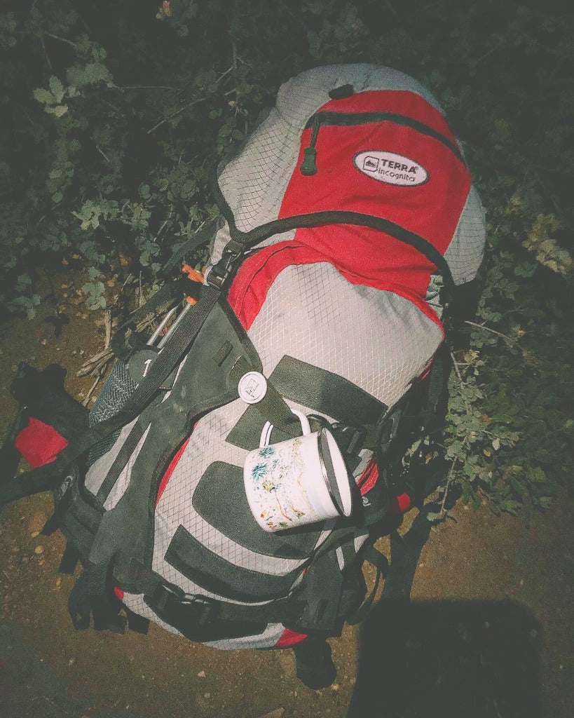 Travel backpack with the Couloir camp mug attached to it in the woods