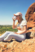 Load image into Gallery viewer, A girl hiker drinks coffee with a scenic view of downtown Phoenix from the made in arizona enamel camp mug with prickly pear design